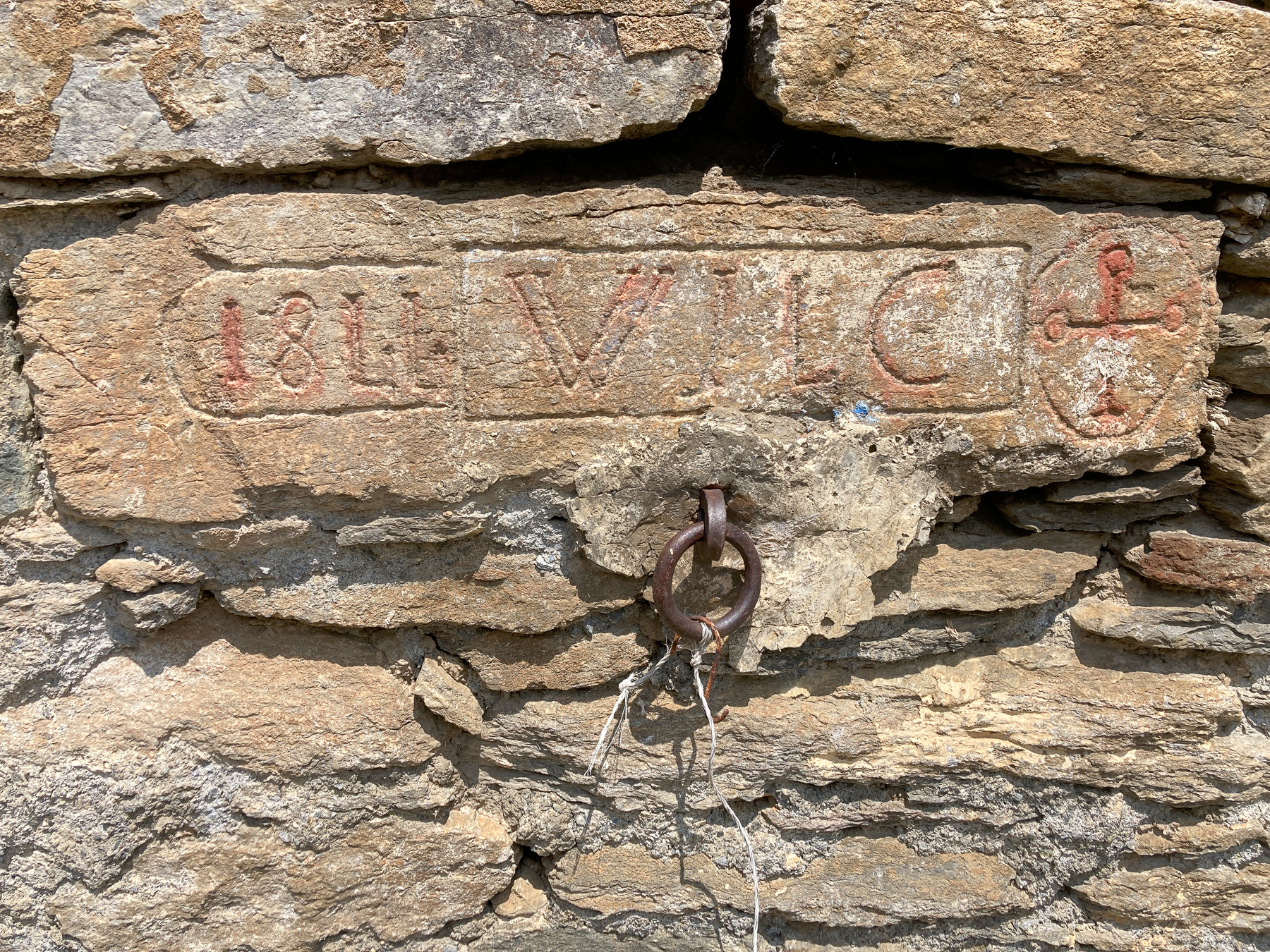 Carved stone on a wall in Faussimagna, 2020